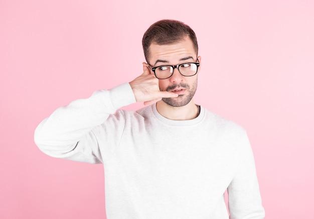Молодой красавец с бородой, делая телефонный жест рукой и пальцами на розовом фоне.