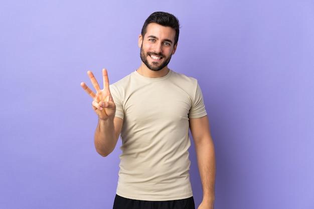 Молодой красавец с бородой счастлив и считает три пальцами