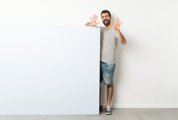 Молодой красавец с бородой, проведение большой синий пустой плакат, считая десять с пальцами