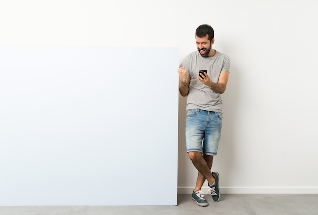 Young handsome man with beard holding a big blue empty placard with phone in victory position