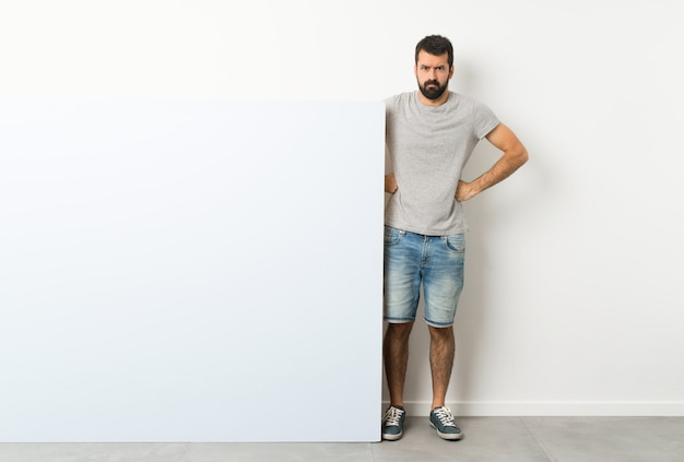 Young handsome man with beard holding a big   empty placard angry