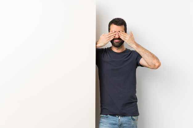Young handsome man with beard holding a big empty placard covering eyes by hands