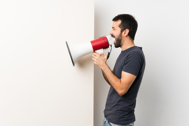 Young handsome man with beard holding a big empty placard shouting through a megaphone