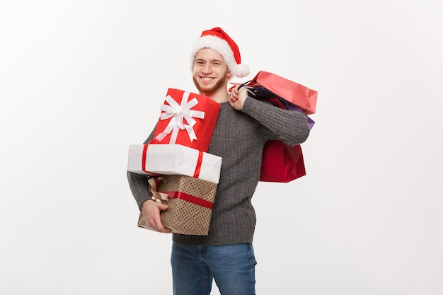 Young handsome man with beard holding a lot of presents and shopping bags with happy facial expression on white