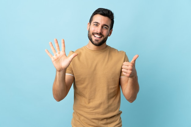 Young handsome man with beard isolated counting six with fingers