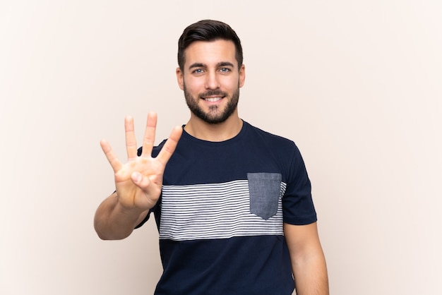 Young handsome man with beard isolated happy and counting four with fingers