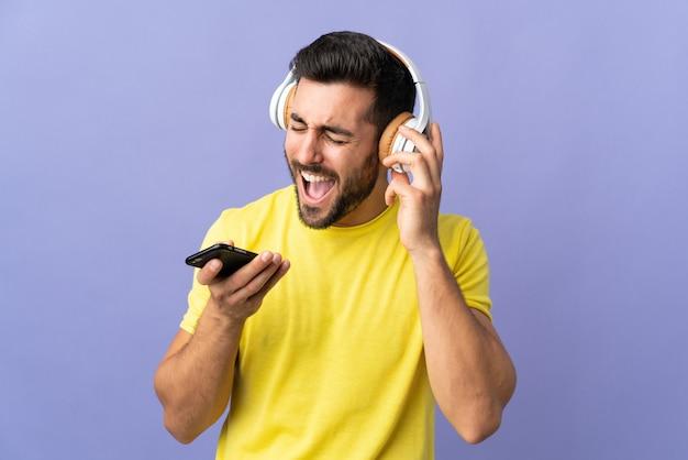Молодой красавец с бородой изолирован на фиолетовом, слушает музыку с мобильным телефоном и поет