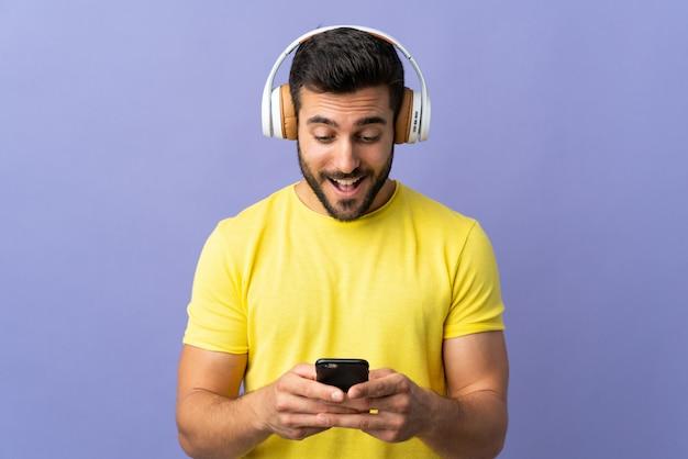 Молодой красавец с бородой, изолированные на фиолетовый стене прослушивания музыки и глядя на мобильный