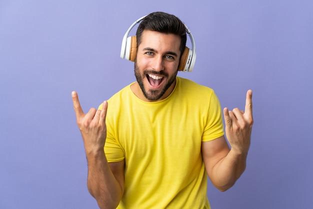 Молодой красавец с бородой, изолированные на фиолетовый стена прослушивания музыки, делая жест рок