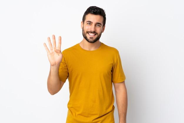 Молодой красавец с бородой, изолированные на белой стене счастливым и считать четыре с пальцами