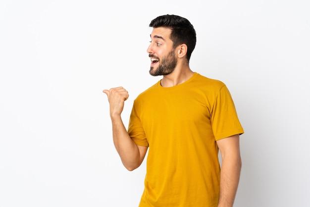 Молодой красавец с бородой изолирован на белой стене, указывая в сторону, чтобы представить продукт
