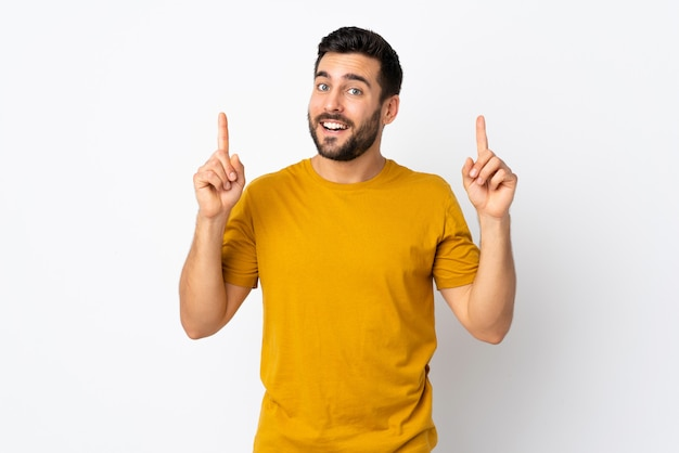 Молодой красавец с бородой, изолированные на белой стене, указывая отличная идея