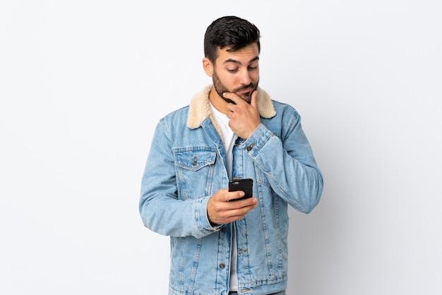 白い壁の思考とメッセージの送信に分離されたひげを持つ若いハンサムな男