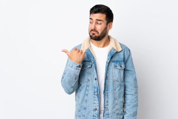 不幸で横を指している白い壁に孤立したひげを持つ若いハンサムな男
