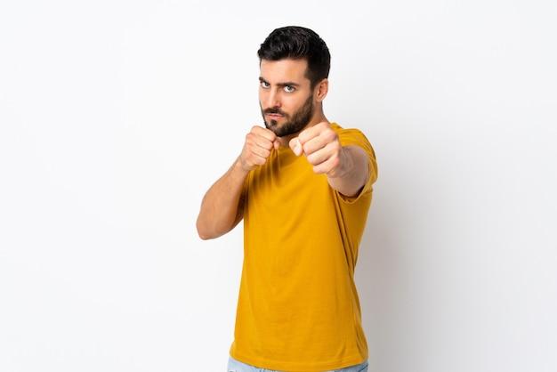Молодой красавец с бородой изолирован на белой стене с боевым жестом