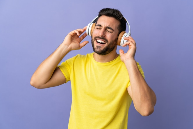 Young handsome man with beard isolated on purple wall listening music and singing