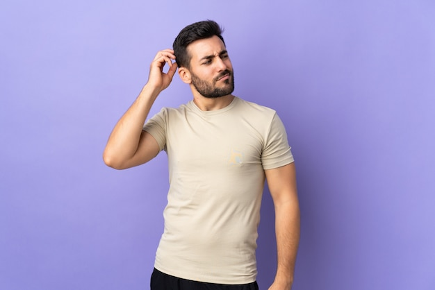 Young handsome man with beard over isolated wall having doubts while scratching head
