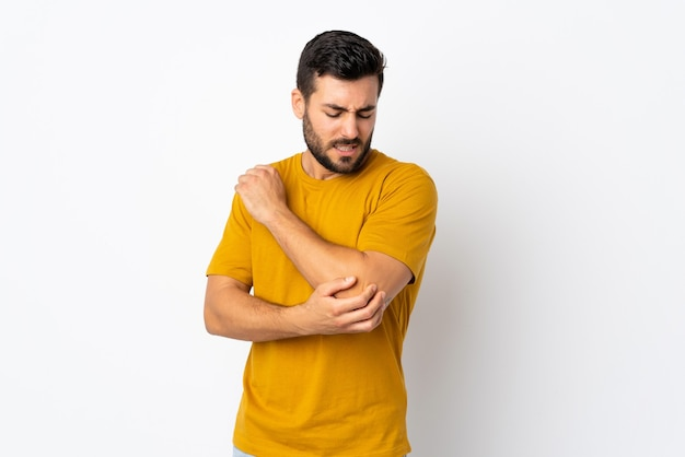 Young handsome man with beard isolated on white background with pain in elbow