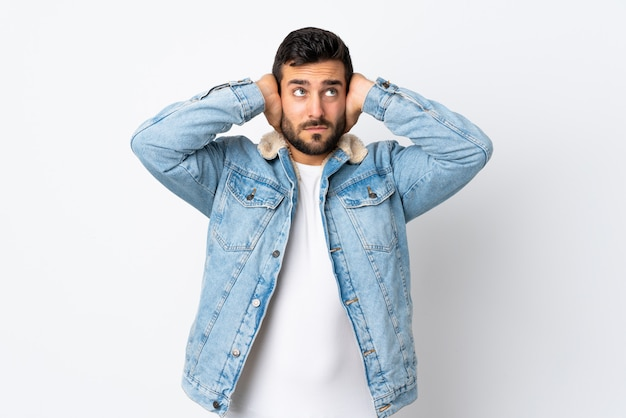 Young handsome man with beard isolated on white frustrated and covering ears