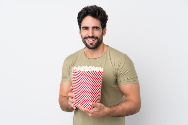 Young handsome man with beard over isolated white wall holding a big bucket of popcorns