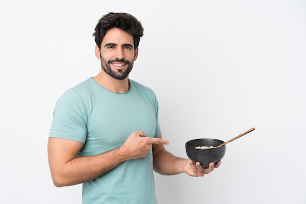 Young handsome man with beard over isolated white wall and pointing it while holding a bowl of noodles with chopsticks