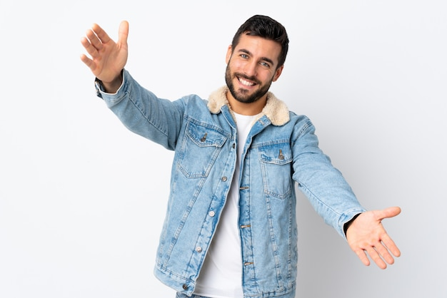 Young handsome man with beard isolated on white wall presenting and inviting to come with hand