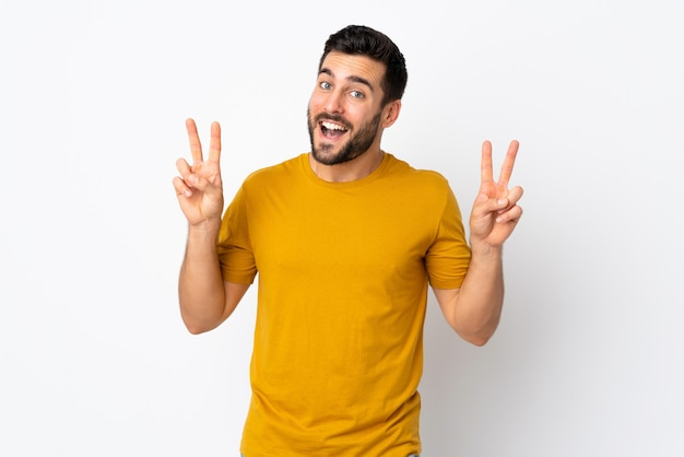 Young handsome man with beard isolated on white wall showing victory sign with both hands