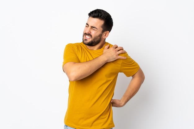 Young handsome man with beard isolated on white wall suffering from pain in shoulder for having made an effort