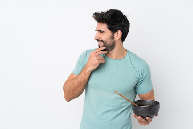 Young handsome man with beard over isolated white wall thinking an idea and looking side while holding a bowl of noodles with chopsticks