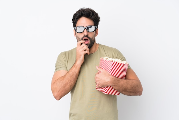 Young handsome man with beard over isolated white wall with 3d glasses and holding a big bucket of popcorns