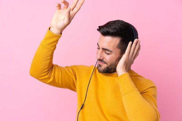 Young handsome man with beard listening music over pink