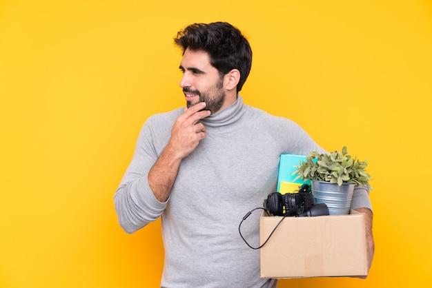 Молодой красавец с бородой, делая ход, поднимая коробку с вещами через изолированную стену, думая идею и глядя в сторону
