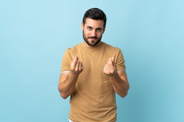 Young handsome man with beard making money gesture but is ruined