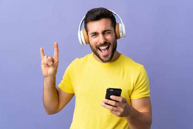 Молодой красавец с бородой на фиолетовый стене прослушивания музыки с мобильного телефона, делая рок жест