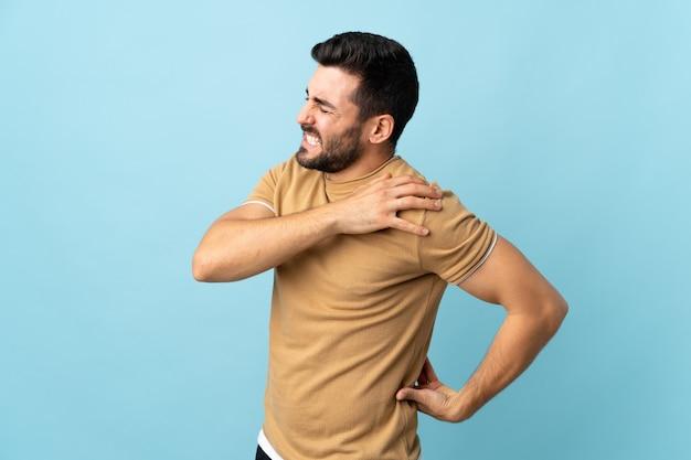 Молодой красавец с бородой на изолированном фоне страдает от боли в плече за то, что приложил усилие