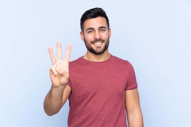 격리 된 파란색 배경 위에 수염을 가진 젊은 잘 생긴 남자 행복하고 손가락으로 세 세