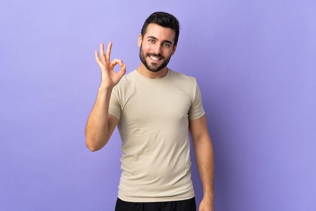 指でokサインを示す孤立した上にひげを持つ若いハンサムな男