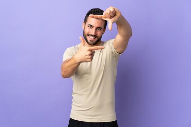Молодой красивый человек с бородой на изолированной стене, фокусировки лица. обрамление символ
