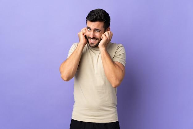 Молодой красавец с бородой над изолированной стеной разочарование и охватывающих уши