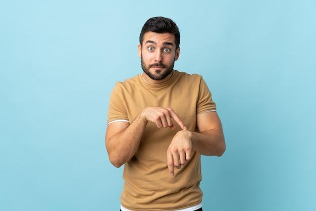 Молодой красивый мужчина с бородой над стеной, делая жест опоздания