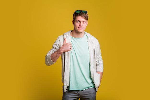 행복 한 얼굴을보고 웃 고 엄지 손가락으로 측면을 가리키는 노란색 벽 위에 서있는 수염을 가진 젊은 잘 생긴 남자.