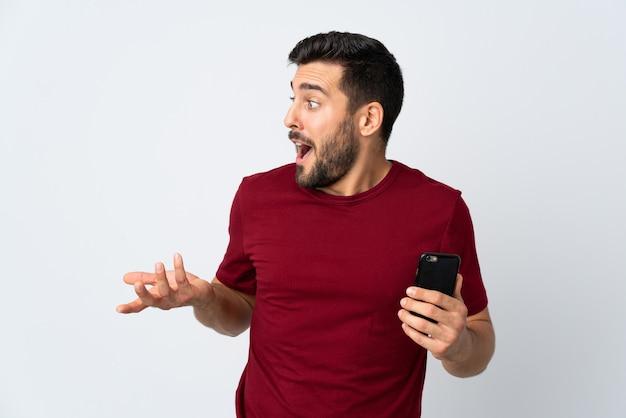 Молодой красавец с бородой с помощью мобильного телефона на белом фоне с удивленным выражением лица