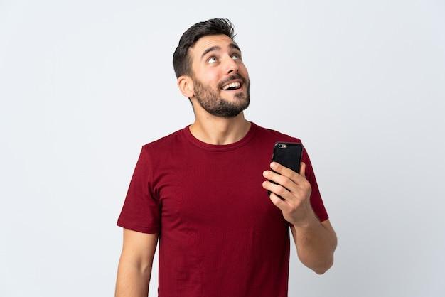 笑顔で見上げる白で隔離の携帯電話を使用してひげを持つ若いハンサムな男