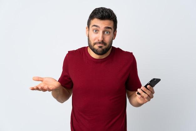 肩を持ち上げている間疑問ジェスチャーを作る白い壁に分離された携帯電話を使用してひげを持つ若いハンサムな男