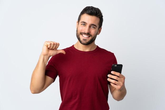 誇らしげで自己満足の白い壁に隔離された携帯電話を使用してひげを持つ若いハンサムな男