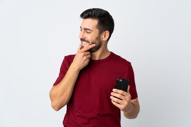 アイデアを考えて側を見ている白い壁に分離された携帯電話を使用してひげを持つ若いハンサムな男