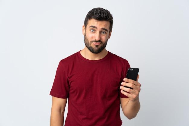 슬픈 표정으로 흰색에 고립 된 휴대 전화를 사용하는 수염을 가진 젊은 잘 생긴 남자