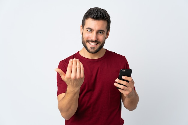 Young handsome man with beard using mobile phone isolated on white background inviting to come with hand. happy that you came