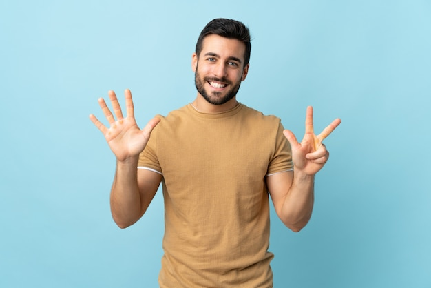 Young handsome man with beard over wall counting eight with fingers