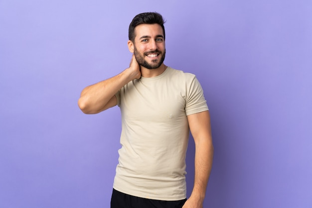 Young handsome man with beard over wall laughing